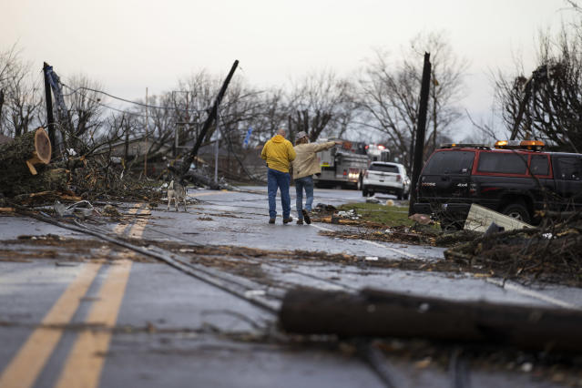 Residents walk through downed utility lines and trees to survey damage caused by one of several tornadoes that tore through the state overnight on March 3, 2020 in Cookeville, Tennessee. At least 19 people were killed and scores more injured in storms across the state that caused severe damage in downtown Nashville. (Brett Carlsen/Getty Images)