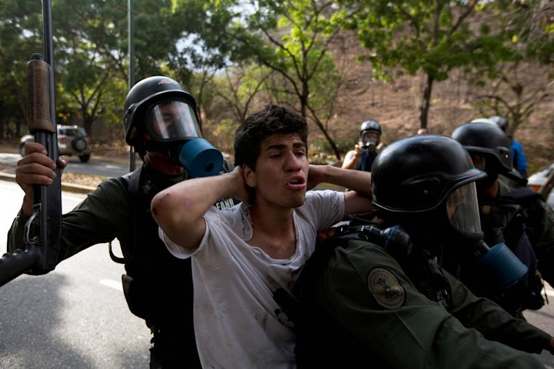 A n anti-government demonstrator is detained by Bolivarian national Guards during a protest in Caracas, Venezuela, Saturday, April 26, 2014. Student organizers at the last minute decided against marching downtown to avoid a confrontation with security forces in the government-controlled district. Instead they concentrated in the wealthier, eastern neighborhoods that have been the hotbed of unrest since February. (AP Photo/Fernando Llano)