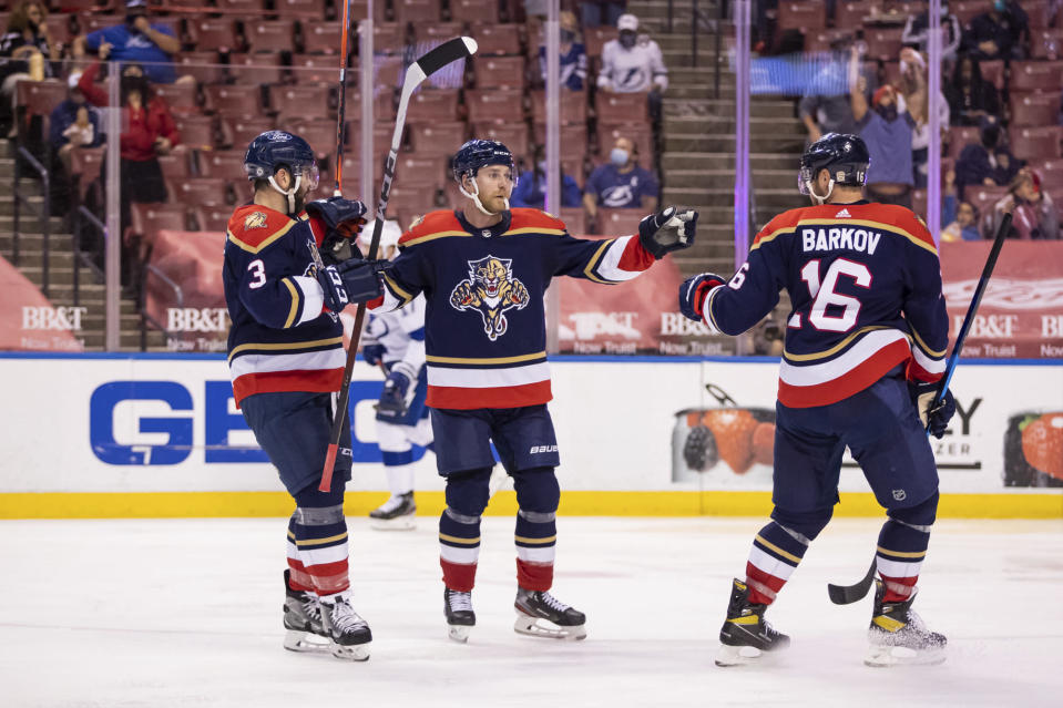 Florida Panthers center Sam Bennett (9) celebrates after scoring a goal with defenseman Keith Yandle (3) and center Aleksander Barkov (16) during the second period of an NHL hockey game against the Tampa Bay Lightning, Saturday, May 8, 2021, in Sunrise, Fla. (AP Photo/Mary Holt)