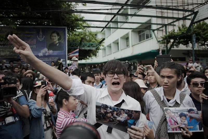 Supporters of anti-coup activists gather outside a police station on June 24, 2015, cheering them on and holding up photos of the protesters who were pulled away by police last month in Bangkok (AFP Photo/Nicolas Asfouri)