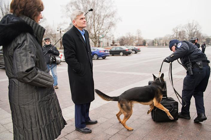Sen. Bill Cassidy (R-La.) and his wife, Laura, have their luggage inspected by a police dog before boarding a bus that will take Republican senators to a retreat in Hershey, Pa., January 14, 2015.