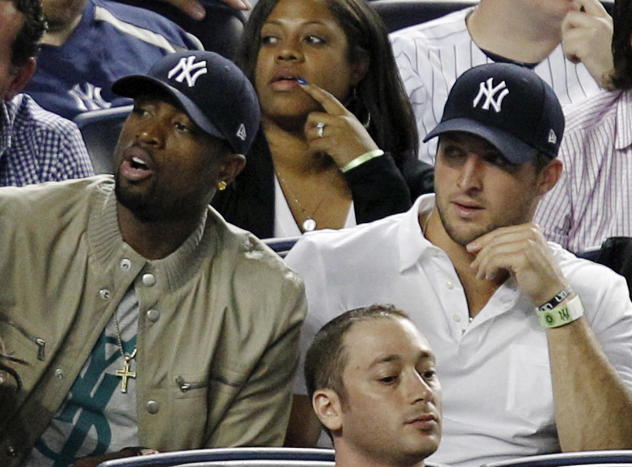 Miami Heat's Dwayne Wade, left, sits beside New York Jets quarterback Tim Tebow during the New York Yankees baseball game against the Los Angeles Angels at Yankee Stadium in New York, Sunday, April 15, 2012. (AP Photo/Kathy Willens)