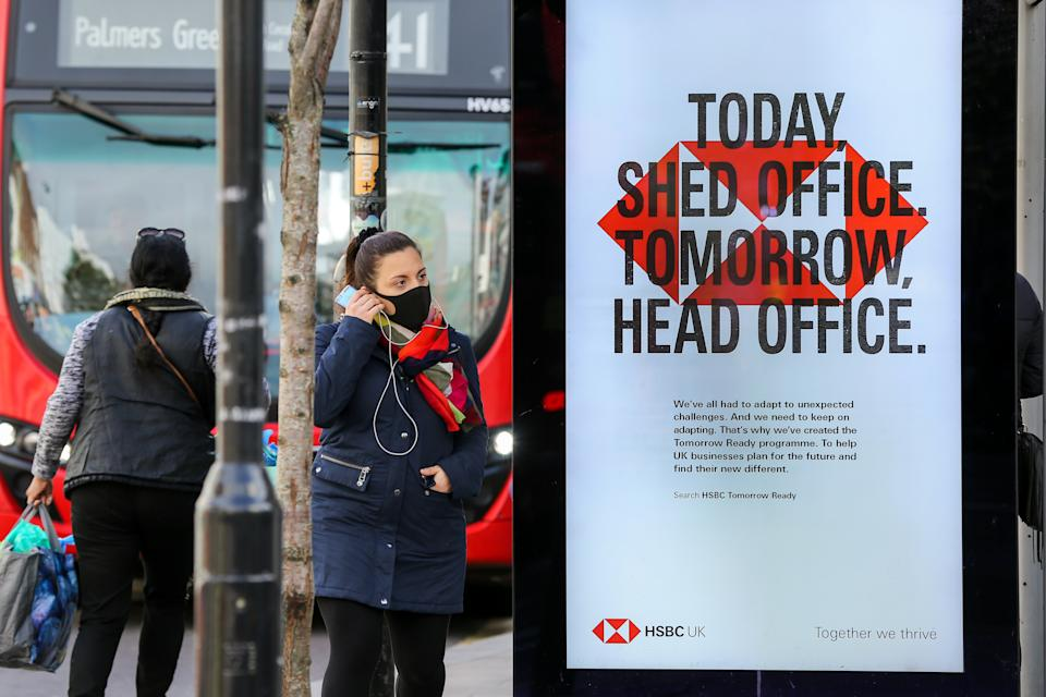 A woman wearing a face mask stands next to a HSBC bank's poster in London. (Photo by Dinendra Haria / SOPA Images/Sipa USA)