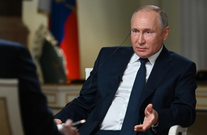 Russian President Vladimir Putin speaks to NBC News journalist Keir Simmons, back to a camera, in an interview aired on Monday, June 14, 2021, two days before the Russian leader is to meet U.S. President Joe Biden in Geneva. Putin has sharply dismissed allegations that his country is carrying out cyberattacks against the United States as baseless. (Maxim Blinov, Sputnik, Kremlin Pool Photo via AP)