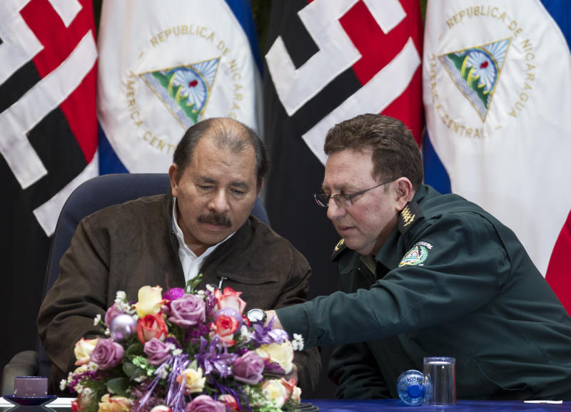 """FILE - In this Dec 5, 2012 file photo, Nicaragua's President Daniel Ortega, left, and Nicaragua's Army Commander Gen. Julio Cesar Aviles Castillo speak during the closing ceremony of an annual defense course at the """"Casa de los Pueblos"""" in Managua, Nicaragua. The U.S. Treasury announced sanctions Friday, May 22, 2020 against Aviles Castillo and one other high-ranking Nicaraguan official for their support of government crackdowns on protesters. (AP Photo/Esteban Felix, File)"""