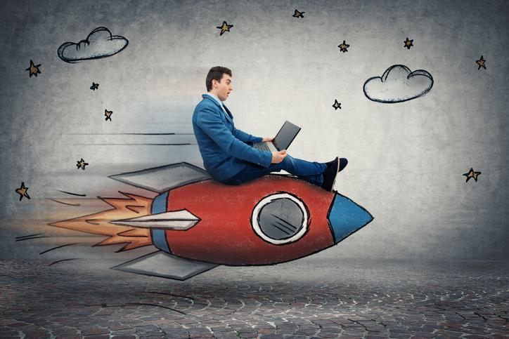 A businessman looking at his laptop while riding a cartoon rocket.