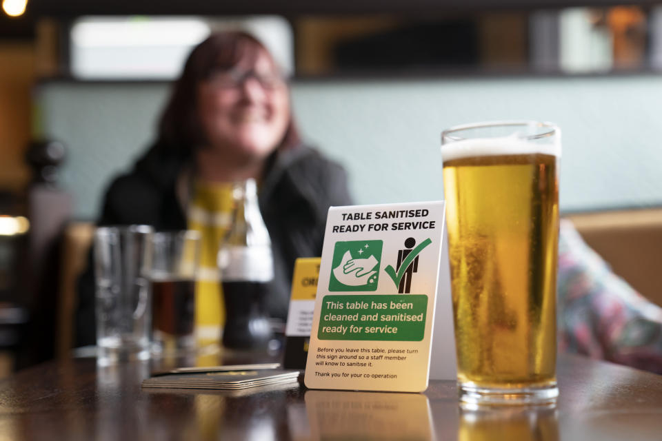 A woman sits in a pub, as pubs, cafes and restaurants in England reopen indoors under the latest easing of the coronavirus lockdown, in Manchester, England, Monday, May 17, 2021. Pubs and restaurants across much of the U.K. are opening for indoor service for the first time since early January even as the prime minister urged people to be cautious amid the spread of a more contagious COVID-19 variant. (AP Photo Jon Super)