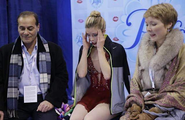 Ashley Wagner, middle, reacts after competing in the women's free skate as her coaches Rafael Arutunian, left, and Nadia Kanaeva, right, look on at the U.S. Figure Skating Championships Saturday, Jan. 11, 2014 in Boston. (AP Photo/Steven Senne)