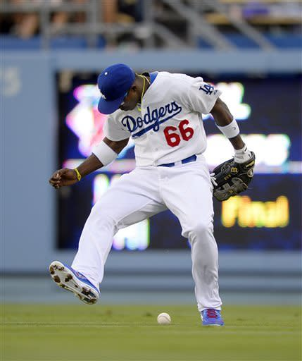 Los Angeles Dodgers right fielder Yasiel Puig can't handle a ball hit for an RBI single by catcher Yasmani Grandal during the second inning of their baseball game, Wednesday, June 5, 2013, in Los Angeles. (AP Photo/Mark J. Terrill)
