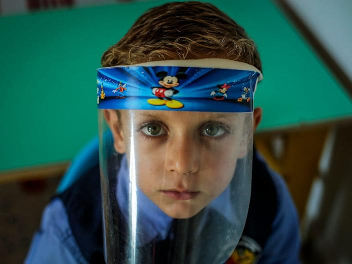 A Palestinian kindergarten child wearing a face shield as a...