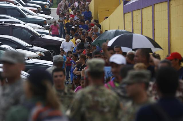 <p>Victims of Hurricane Maria line up to receive supplies from members of the U.S. military, in Las Piedras, Puerto Rico, Oct. 18, 2017. (Photo: Thais Llorca/EPA-EFE/REX/Shutterstock) </p>