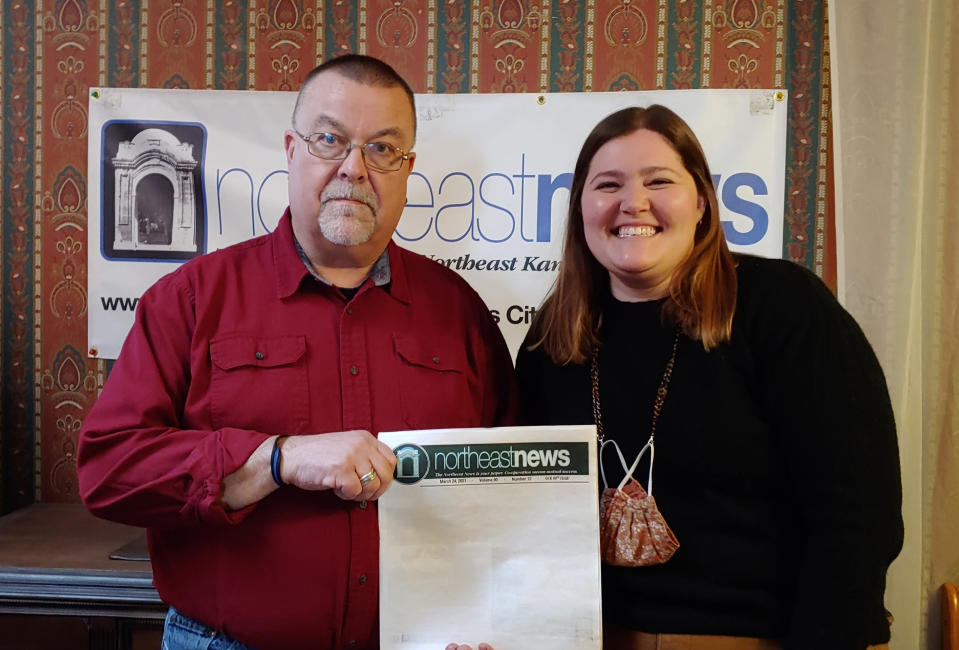 Publisher Michael Bushnell, left, and Managing Editor Abby Hoover pose in the offices of The Northeast News, a community paper in Kansas City, Mo., on March 31, 2021. The paper chose to leave the front page of their March 24 issue blank to show community members what they'd miss if the newspaper folded. (The Northeast News via AP)