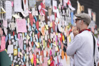 A man looks at the messages of support left on a mural of Manchester United striker and England player Marcus Rashford, on the wall of the Coffee House Cafe on Copson Street, in Withington, Manchester, England, Tuesday July 13, 2021. The mural was defaced with graffiti in the wake of England losing the Euro 2020 soccer championship final match to Italy. (AP Photo/Jon Super)