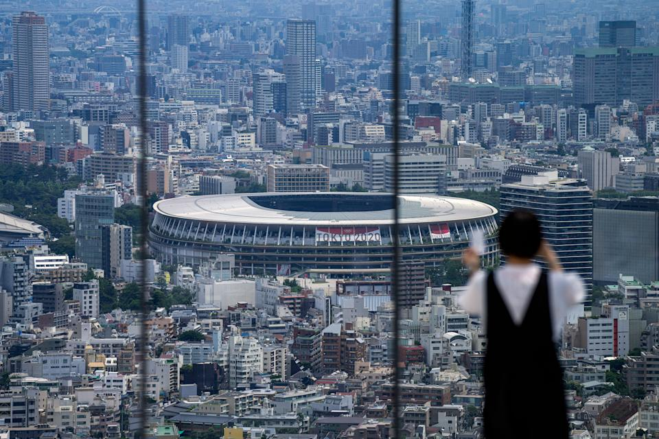 A person wearing a protective mask takes a picture from an observation deck as National Stadium, where the opening ceremony of the Tokyo Olympics will be held, is seen in the background.