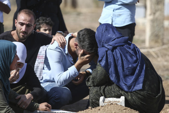 Relatives of Halil Yagmur, 64, who was killed Friday during mortar shelling from Syria, mourn over his grave at the cemetery in the town of Suruc, southeastern Turkey, at the border with Syria, Saturday, Oct. 12, 2019. Turkey says its military offensive has taken central Ras al-Ayn, a key border town in northeastern Syria, and its most significant gain since its cross-border operation began against Syrian Kurdish fighters began. (AP Photo/Emrah Gurel)