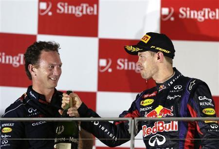 Red Bull team principal Christian Horner (L) celebrates on the podium with Red Bull Formula One driver Sebastian Vettel of Germany after Vettel won the Singapore F1 Grand Prix at the Marina Bay street circuit in Singapore September 22, 2013. REUTERS/Pablo Sanchez