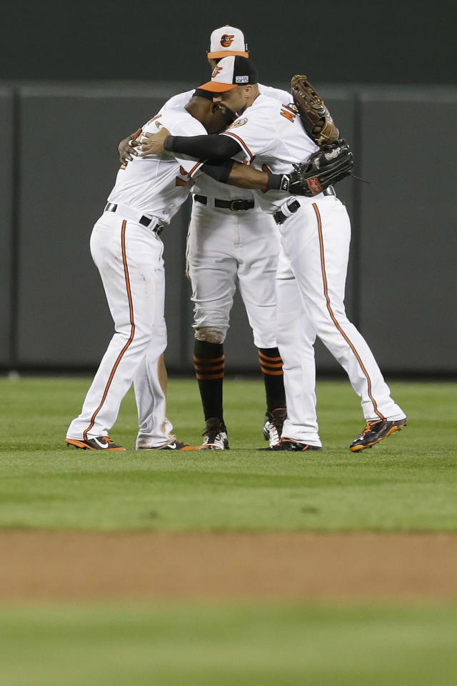Baltimore Orioles left fielder Alejandro De Aza, left, center fielder Adam Jones, rear, and right fielder Nick Markakis celebrate after Game 1 of baseball's AL Division Series against Detroit Tigers in Baltimore, Thursday, Oct. 2, 2014. The Orioles defeated the Tiger 12-3. (AP Photo/Patrick Semansky)