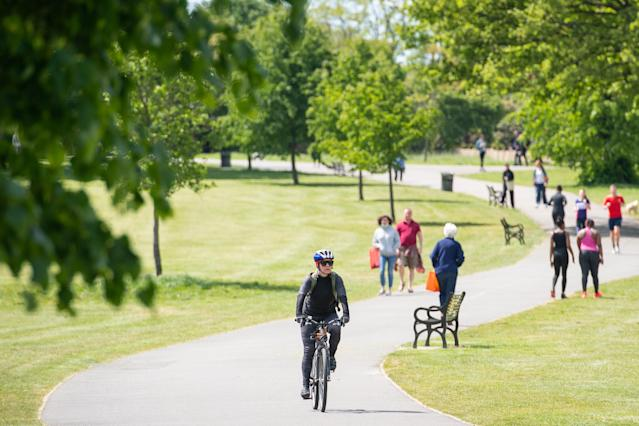 People walk and exercise in the sun in Brockwell Park, south London. (PA via Getty Images)
