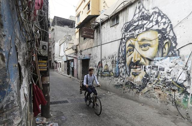 Mohammed rides his bicycle past a mural painting of the late Palestinian leader Yasser Arafat south of the Lebanese capital Beirut on May 29, 2018 (AFP Photo/JOSEPH EID)