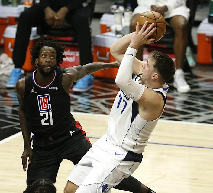 Dallas Mavericks guard Luka Doncic attempts a basket guarded by Clippers guard Patrick Beverley.