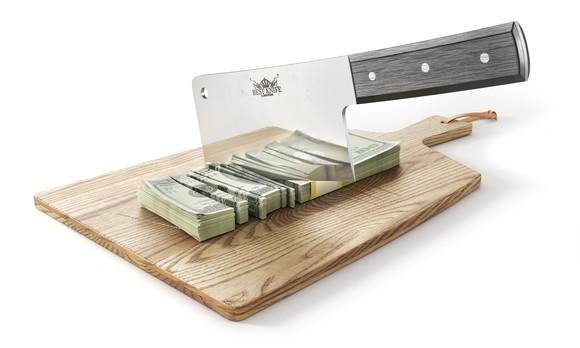 A cleaver slicking through a stack of U.S. hundred-dollar bills on a wooden cutting board.