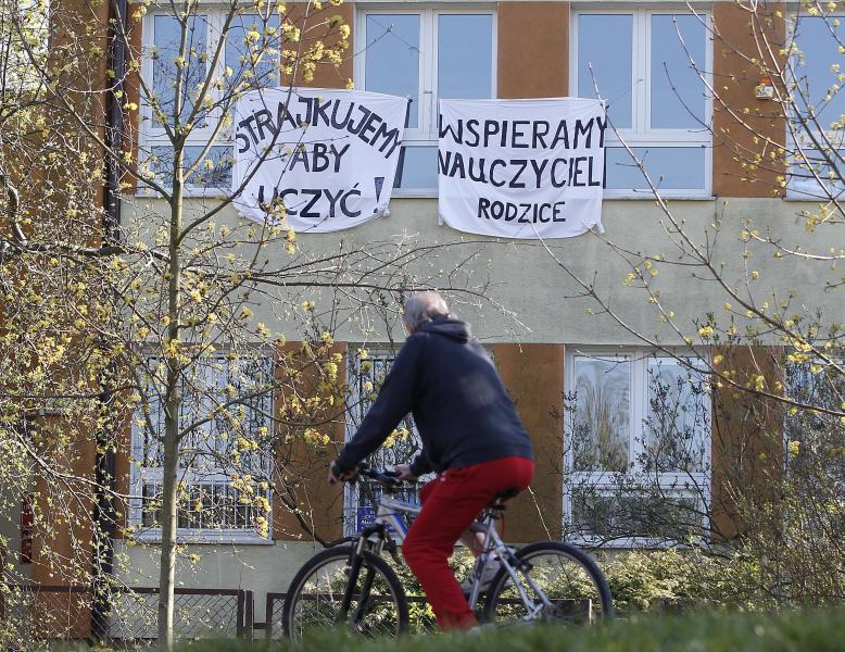 A cyclist rides by a school where teachers are taking part in nationwide pay strike, with banners declaring the participation in the strike and also parent's support for it, in Warsaw, Poland, on Monday, April 15, 2019. The right-wing government says it has money only to grant half of the teachers' demands in a sign that its policy of pre-election spending has reached its limit.(AP Photo/Czarek Sokolowski)
