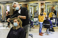 Richard Ward, owner of Richard Ward Hair & MetroSpa wears a protective face mask as he works in his salon in London, Wednesday, Nov. 4, 2020. Britain is preparing to join large swathes of Europe in a coronavirus lockdown designed to save its health care system from being overwhelmed. Pubs, along with restaurants, hairdressers and shops selling non-essential items will have to close Thursday until at least Dec. 2. (AP Photo/Alberto Pezzali)