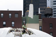 A worker guides a marble roof panel into place at the St. Nicholas Greek Orthodox Church, Wednesday, Sept. 8, 2021, at the World Trade Center in New York. The construction of the only house of worship destroyed in the attacks of September 11, 2001, is now proceeding briskly after years of delays. (AP Photo/Mark Lennihan)