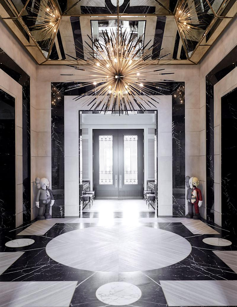 Two sculptures by Kaws flank the home's entrance. Custom bronze-and-solid-marble chandelier by Rafauli; Escarpment Light and Nero Marquina marble cover the floor.