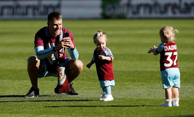 "Soccer Football - Premier League - Burnley vs AFC Bournemouth - Turf Moor, Burnley, Britain - May 13, 2018 Burnley's Johann Berg Gudmundsson celebrates with his children during a lap of honour after the match Action Images via Reuters/Craig Brough EDITORIAL USE ONLY. No use with unauthorized audio, video, data, fixture lists, club/league logos or ""live"" services. Online in-match use limited to 75 images, no video emulation. No use in betting, games or single club/league/player publications. Please contact your account representative for further details."