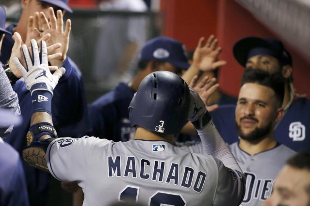San Diego Padres' Manny Machado, center, celebrates his home run against the Arizona Diamondbacks with teammates, including Luis Torrens, right, during the sixth inning of a baseball game Friday, Sept. 27, 2019, in Phoenix. (AP Photo/Ross D. Franklin)