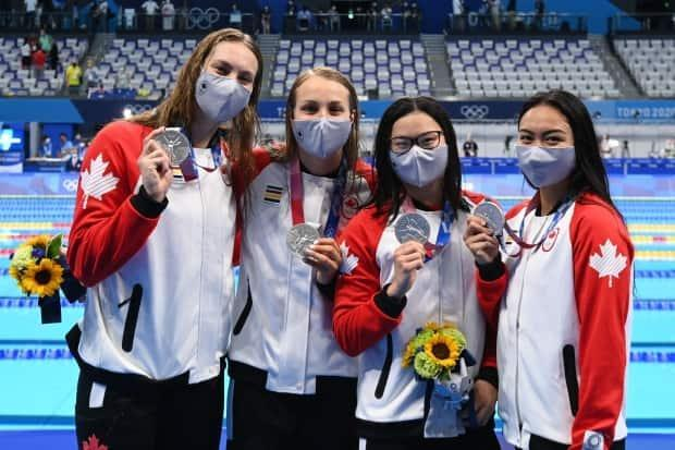 From left to right, Penny Oleksiak, Rebecca Smith, Maggie Mac Neil and Kayla Sanchez pose after the 4x100m freestyle relay swimming final at the Tokyo Aquatics Centre in Tokyo on Sunday. The foursome won Canada's first medal at the Tokyo Games, and the other eight have also been captured by women athletes. (Attila Kisbenedek/AFP via Getty Images - image credit)