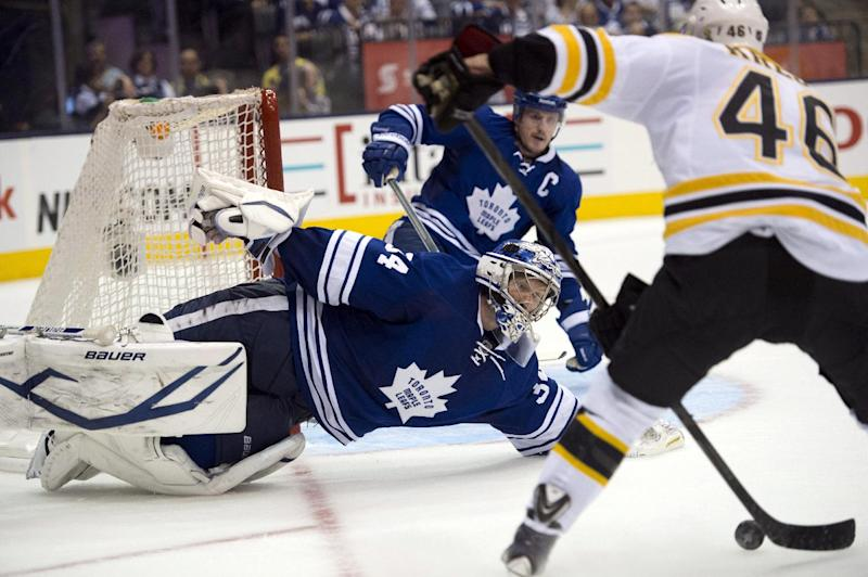 Toronto Maple Leafs goaltender James Reimer makes a diving save on Boston Bruins' David Krejci, right, during the third period of Game 4 of their NHL hockey Stanley Cup playoff series, Wednesday, May 8, 2013, in Toronto. (AP Photo/The Canadian Press, Frank Gunn)