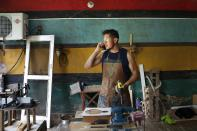 Goalkeeper Jorge Chena of the second division Atyra F.C., speaks on his mobile phone inside his workshop in Nemby, Paraguay, Sunday, Jan. 31, 2021. Chena, 32, who has played 13 years as a professional, now works as a carpenter after spending a year without being paid by his club due to the COVID-19 pandemic. (AP Photo/Jorge Saenz)