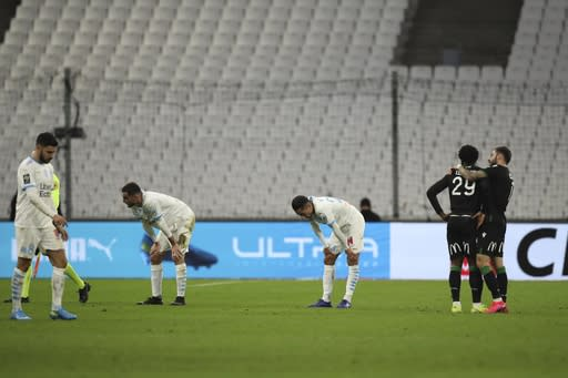 Marseille players react after the French League One soccer match between Marseille and Lens at the Veledrome stadium in Marseille, France, Wednesday, Jan. 20, 2021. Lens won 1-0. (AP Photo/Daniel Cole)