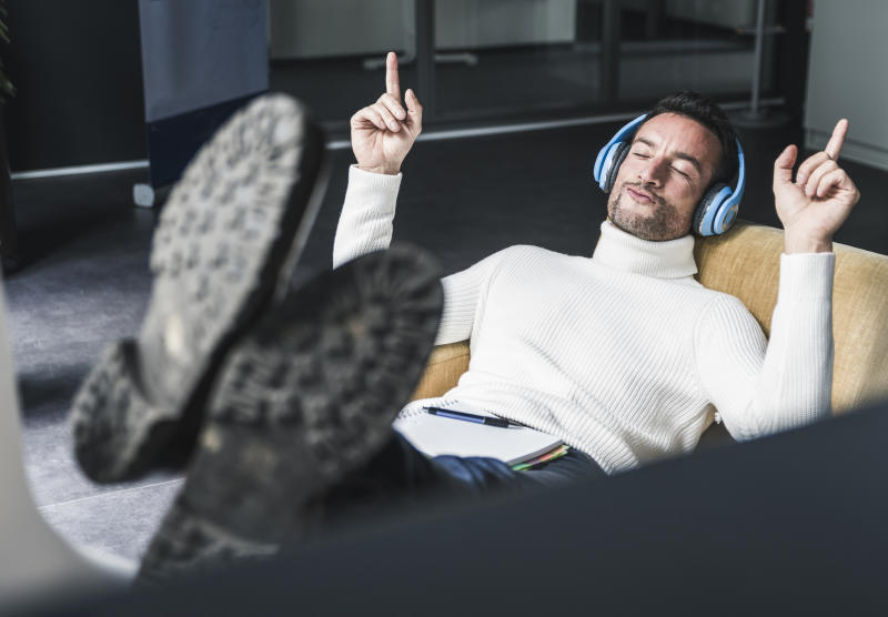 Businessman listening relaxed music in his office