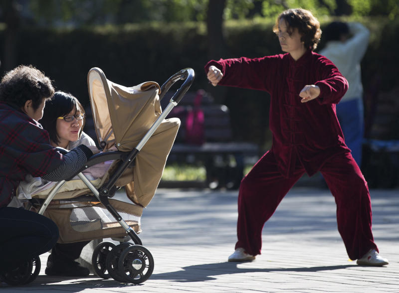 A Chinese woman performs a morning exercise next to a family members having a light moment with their infant at the Ritan Park in Beijing Wednesday, Oct. 31, 2012. A government think tank says China should start phasing out its one-child policy immediately and allow two children for every family by 2015. It remains unclear whether Chinese leaders are ready to take that step. (AP Photo/Andy Wong)