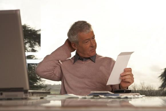 A senior man scratching his head while sitting at a desk looking at a piece of paper.