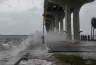 A reporter is splashed by waves as strong gusts of wind and bands of heavy rain hit the Jensen Beach Causeway Park in Florida.