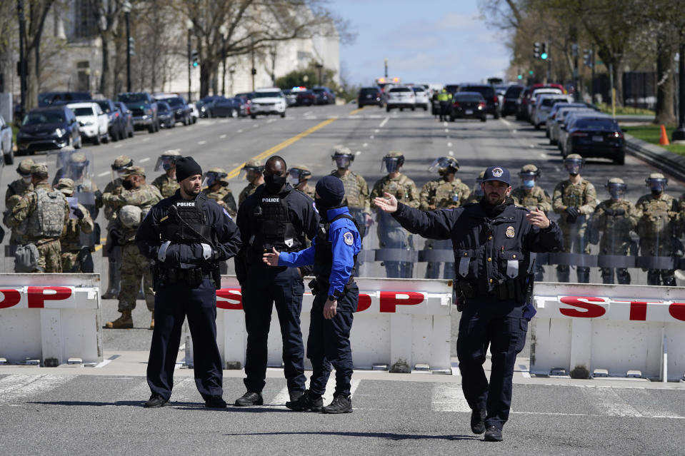 Members of the U.S. Capitol Police stand guard near the scene of a car that crashed into a barrier on Capitol Hill in Washington, Friday, April 2, 2021. (AP Photo/Patrick Semansky)
