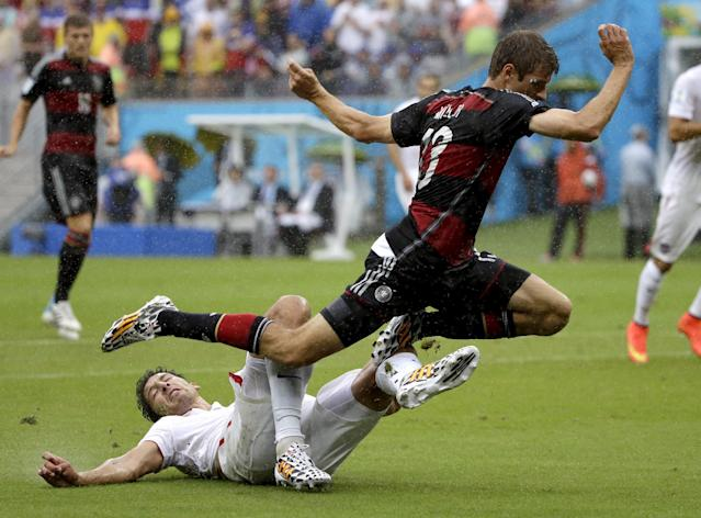 Germany's Thomas Mueller is tripped by United States' Omar Gonzalez during the group G World Cup soccer match between the USA and Germany at the Arena Pernambuco in Recife, Brazil, Thursday, June 26, 2014. (AP Photo/Ricardo Mazalan)