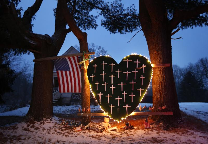 FILE - In this Saturday, Dec. 14, 2013, file photo, a makeshift memorial with crosses for the victims of the Sandy Hook massacre stands outside a home in Newtown, Conn., the one-year anniversary of the shootings. Connecticut authorities said they planned Friday, Dec. 27, 2013, to release state police documents from the investigation into last year's Newtown school massacre. (AP Photo/Robert F. Bukaty, File)