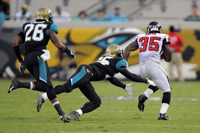 Atlanta Falcons running back Antone Smith (35) breaks away from Jacksonville Jaguars defensive back Sherrod Martin, center, and free safety Josh Evans (26) for a 66-yard touchdown after a reception during the first half of an NFL preseason football game in Jacksonville, Fla., Thursday, Aug. 28, 2014. (AP Photo/Stephen B. Morton)