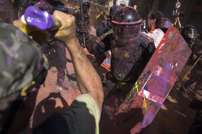 Catalan police officers clash with pro-independence demonstrators on their way to meet demonstrations by member and supporters of National Police and Guardia Civil in Barcelona on Saturday, Sept. 29, 2018. (AP Photo/Emilio Morenatti)