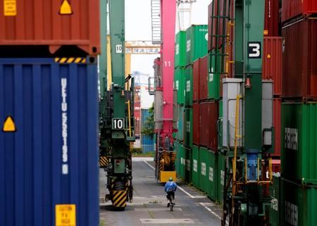FILE PHOTO: A man in a bicycle drives past containers at an industrial port in Tokyo