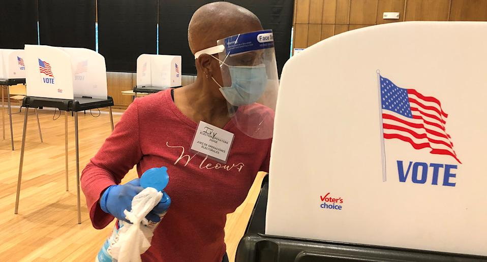 Ivy West, an elections judge, cleaning a booth after someone voted at the Silver Spring Civic Building in Silver Spring, Maryland.