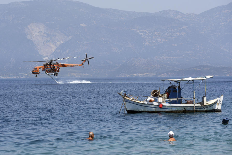 A helicopter fills up with water from the sea near Ziria village, east of Patras, Greece, Sunday, Aug. 1, 2021. A wildfire that broke out Saturday in western Greece forced the evacuation of four villages and people on a beach by the Fire Service, the Coast Guard and private boats, authorities said. (AP Photo/Andreas Alexopoulos)