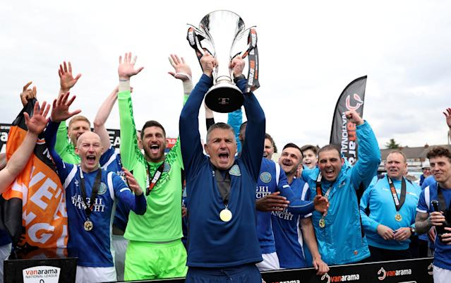 Soccer Football - National League - Macclesfield Town v Dagenham & Redbridge - Moss Rose, Macclesfield, Britain - April 28, 2018 Macclesfield Town manager John Askey celebrates winning the league with their players as he lifts the trophy Action Images/Peter Cziborra