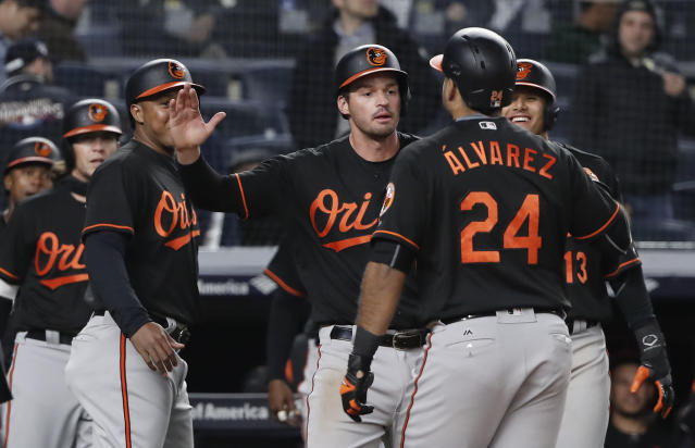 Baltimore Orioles' Pedro Alvarez (24) is greeted by teammates after hitting a grand slam against the New York Yankees in the 14th inning of a baseball game early Saturday, April 7, 2018, in New York. The Orioles won 7-3. (AP Photo/Julie Jacobson)