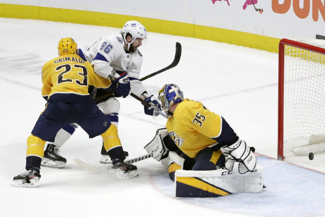 Tampa Bay Lightning right wing Nikita Kucherov (86), of Russia, scores the winning goal past Nashville Predators goaltender Pekka Rinne (35), of Finland, and Rocco Grimaldi (23) in overtime of an NHL hockey game Tuesday, Dec. 3, 2019, in Nashville, Tenn. The Lightning won 3-2. (AP Photo/Mark Humphrey)